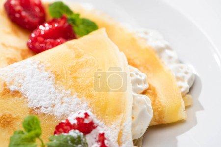 Photo pour Vue rapprochée de crêpes savoureuses aux framboises et crème fouettée sur assiette - image libre de droit