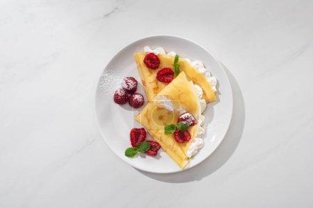 Photo pour Vue de dessus de crêpes savoureuses aux framboises et crème fouettée sur fond gris - image libre de droit