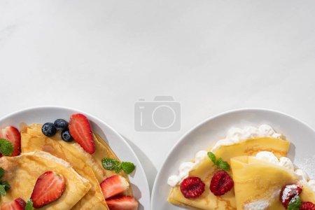 Photo pour Vue de dessus des crêpes savoureuses avec des baies sur des assiettes sur fond gris - image libre de droit
