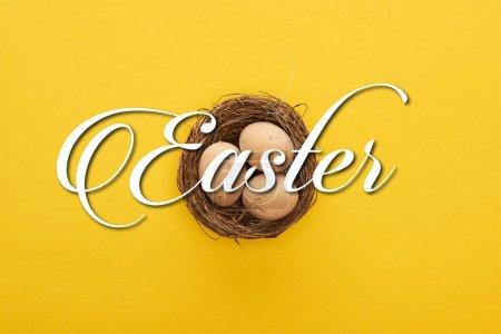Photo pour Vue du dessus des œufs de poulet dans le nid sur fond jaune coloré avec illustration de Pâques - image libre de droit