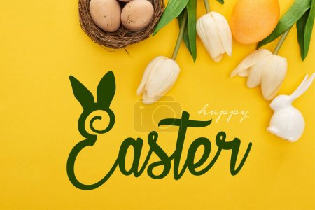 Photo pour Top view of tulips and chicken eggs in nest near Easter bunny on colorful yellow background with happy Easter illustration - image libre de droit