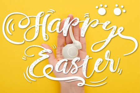 Photo for Cropped view of woman holding white Easter bunny on colorful yellow background with happy Easter illustration - Royalty Free Image