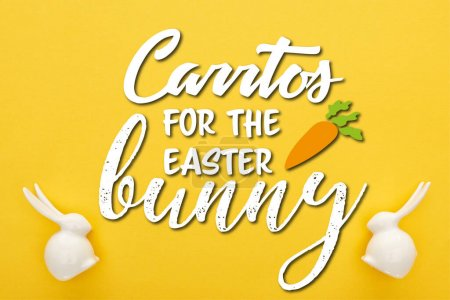 Photo for Top view of white Easter bunnies on colorful yellow background with carrots for the easter bunny illustration - Royalty Free Image