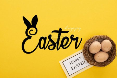 Photo for Top view of greeting card with happy Easter lettering near chicken eggs in nest on yellow colorful background - Royalty Free Image