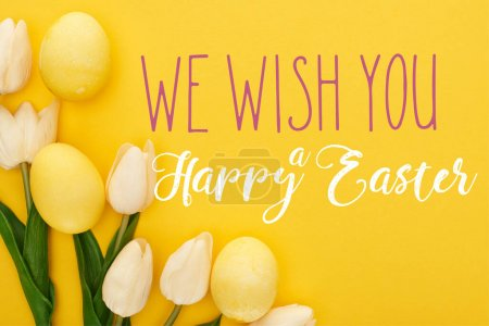 top view of tulips and painted Easter eggs on colorful yellow background with we wish you a happy Easter illustration