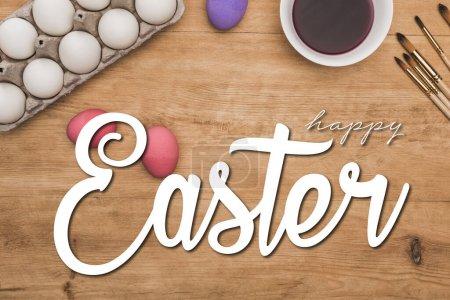 """Photo pour Haut de la page aquarelle peinture violette dans un bol près d """"œufs de poulet peints et de pinceaux sur une table en bois avec une jolie illustration de Pâques - image libre de droit"""