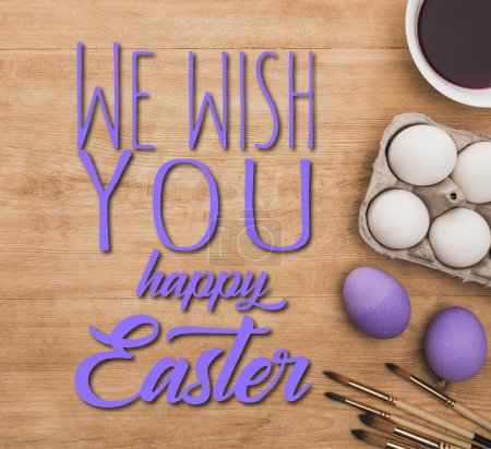 Photo pour Top view of aquarelle violet paint in bowl near chicken eggs and paintbrushes on wooden table with we wish you a happy Easter illustration - image libre de droit
