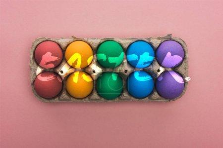 Photo pour Vue du dessus des œufs peints dans une boîte en carton sur fond rose avec illustration de Pâques - image libre de droit