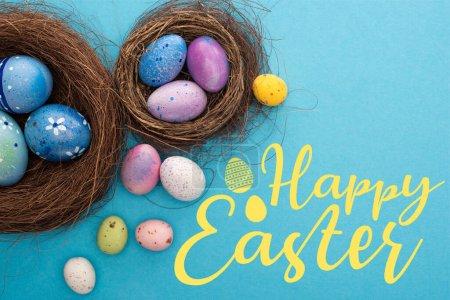 Photo pour Vue du dessus des œufs de Pâques colorés dans les nids sur fond bleu avec une illustration de Pâques heureuse - image libre de droit