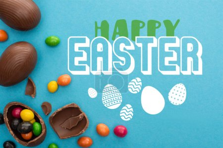 Photo for Top view of chocolate Easter eggs with colorful sweets on blue background with happy Easter illustration - Royalty Free Image
