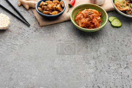 high angle view of bowls with kimchi near chopsticks, ginger, chili pepper, sliced cucumber and garlic on concrete surface