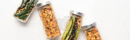 panoramic shot of cucumber and daikon radish kimchi in jars on white background