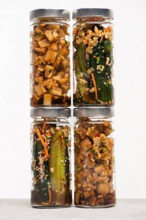 Photo for Cucumber and daikon radish kimchi in glass jars isolated on white - Royalty Free Image