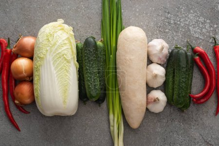 Photo for Top view of chili peppers, green onions, cucumbers, daikon radish, chinese cabbage, onions and garlic on grey concrete background - Royalty Free Image
