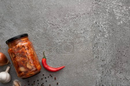 top view of kimchi jar, chili pepper and garlic on concrete surface
