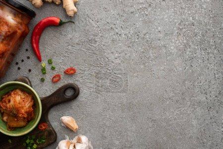 Photo pour Vue du dessus du kimchi dans un bocal et un bol sur une planche à découper près du gingembre, de l'ail et du piment sur une surface en béton - image libre de droit