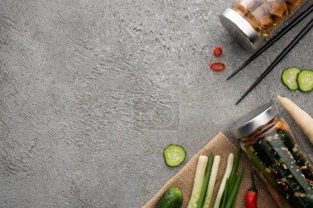 Photo pour Vue de dessus de savoureux kimchi dans des bocaux, baguettes, oignons verts et gingembre sur la surface du béton - image libre de droit