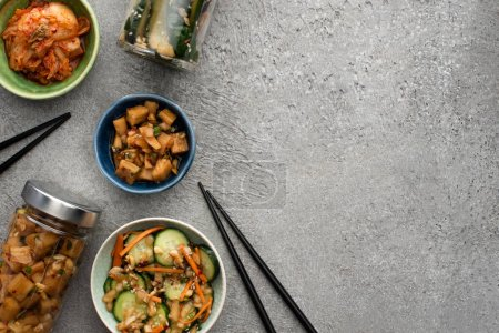 top view of tasty kimchi in bowls and jars near chopsticks on concrete surface