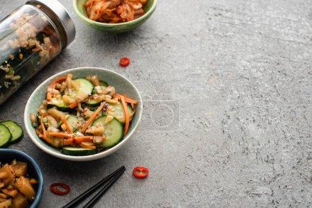 Photo pour Savoureux kimchi dans des bols et des bocaux près de baguettes sur la surface du béton - image libre de droit