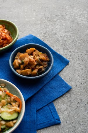Photo pour Bols avec kimchi savoureux sur tissu bleu sur la surface du béton - image libre de droit