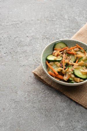 Photo pour Bol de délicieux kimchi concombre sur sac sur la surface du béton - image libre de droit