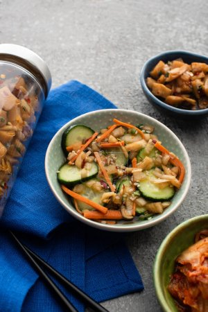 Photo pour Délicieux kimchi dans des bols et bocaux près de baguettes sur tissu bleu sur la surface du béton - image libre de droit