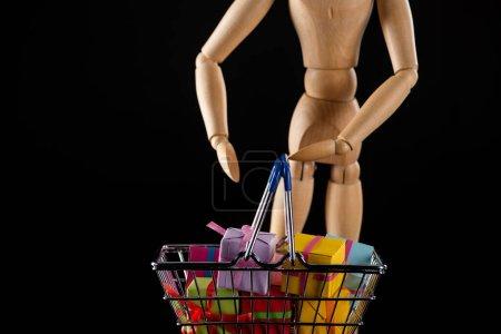 Photo pour Concentration sélective de poupée en bois et cadeaux dans le panier isolé sur noir - image libre de droit