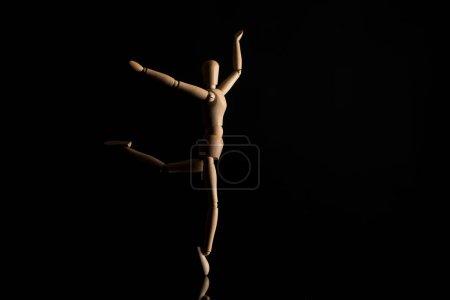 Photo pour Poupée en bois imitant la danse sur fond noir - image libre de droit