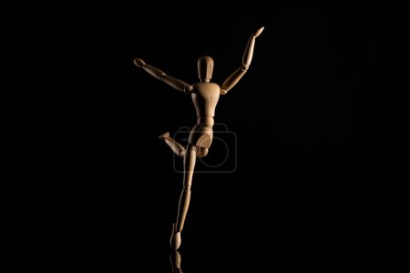 Photo pour Jouet en bois imitant la danse sur noir - image libre de droit