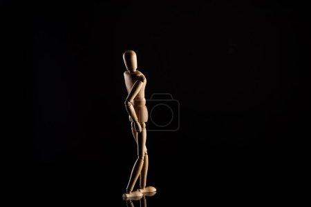 Wooden doll imitating leaning back on black background