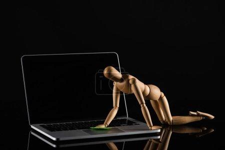 Photo pour Poupée en bois sur les quatre positions imitant ordinateur portable poussiéreux sur fond noir - image libre de droit