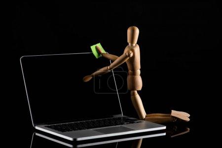 Photo pour Poupée en bois sur les genoux position imitant ordinateur portable poussiéreux sur noir - image libre de droit