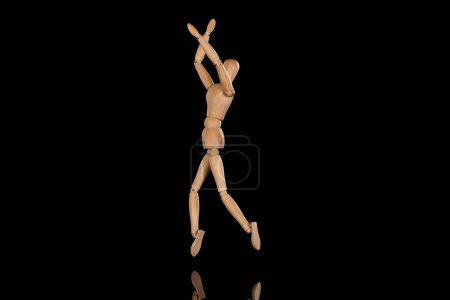 Photo for Wooden doll imitating dancing with crossed arms on black - Royalty Free Image