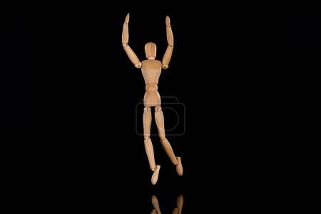 Photo pour Poupée en bois imitant la danse avec les mains tendues sur le noir - image libre de droit