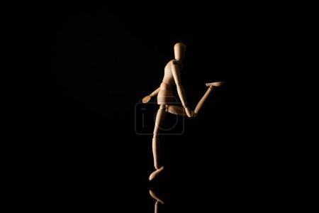 Photo pour Poupée en bois imitant la jambe levante sur fond noir - image libre de droit