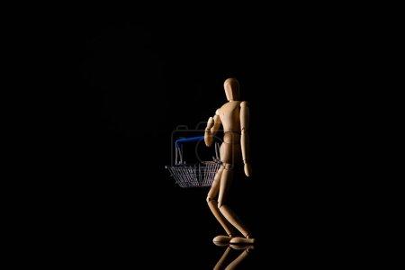 Photo pour Poupée en bois en position debout avec panier sur fond noir - image libre de droit