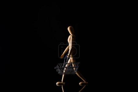 Photo pour Poupée en bois imitant la marche avec panier sur fond noir - image libre de droit