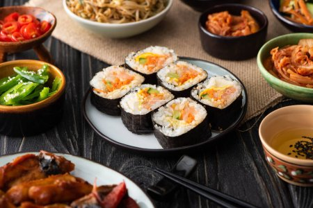 Photo for Selective focus of gimbap with salmon near chopsticks and korean side dishes - Royalty Free Image