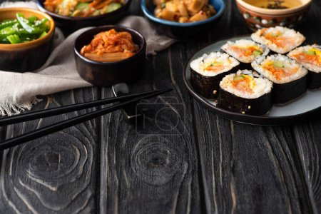 Photo for Selective focus of korean rice rolls near side dishes, chopsticks and cotton napkin on wooden surface - Royalty Free Image