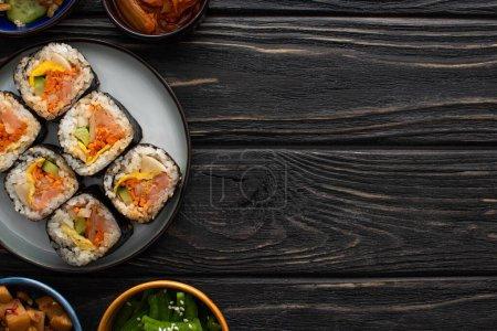 Photo pour Vue de dessus des plats d'accompagnement coréens près de la plaque avec un savoureux gimbap sur la surface en bois - image libre de droit