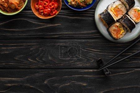 Photo pour Vue de dessus de la plaque avec gimbap coréen et plats d'accompagnement savoureux près de baguettes sur la surface en bois - image libre de droit