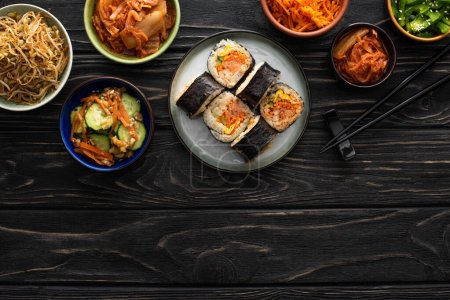 Photo for Top view of plate with gimbap and chopsticks near tasty korean side dishes on wooden surface - Royalty Free Image