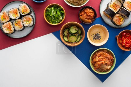 Photo for Top view of plates with fresh gimbap near korean side dishes on white, blue and crimson - Royalty Free Image