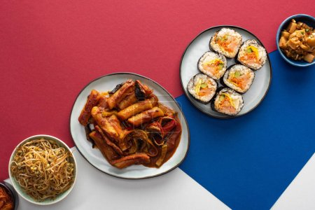 Photo for Top view of fresh tteokbokki  and gimbap near korean side dishes on white, blue and crimson - Royalty Free Image