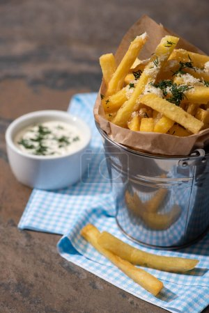 Photo for Selective focus of bucket with salty french fries and creamy garlic sauce on marble surface - Royalty Free Image