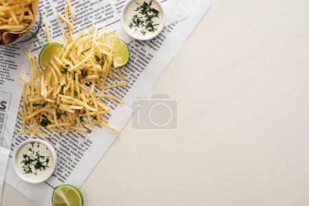 top view of salty french fries, garlic sauce and sliced lime on newspaper on white