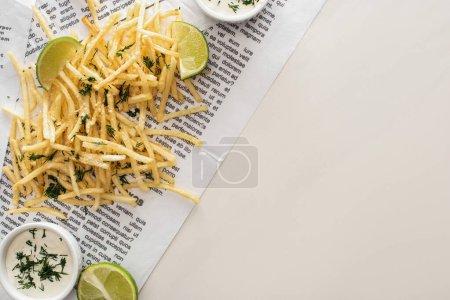 Ansicht von frittierten Pommes frites, Knoblauchsauce und Limettenscheiben auf Zeitung auf Weiß