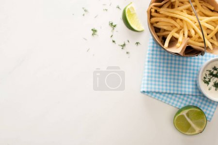 top view of fried french fries, garlic sauce and sliced lime on white