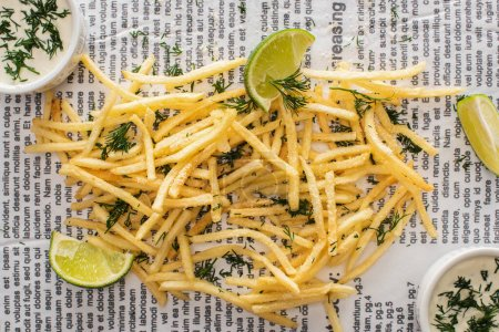 Photo for Top view of crispy french fries with dill near lime and garlic sauce on newspaper - Royalty Free Image
