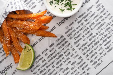 top view of crispy french fries, sliced lime and garlic sauce with dill on newspaper